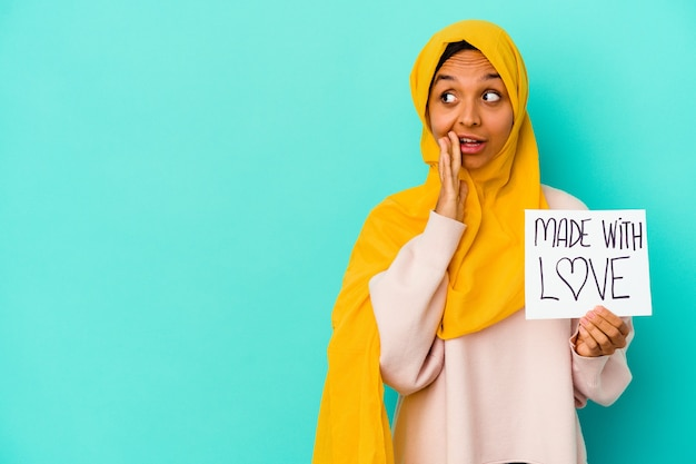 Młoda muzułmanka trzymająca afisz wykonany z miłością na białym tle na niebieskim tle mówi tajne gorące wiadomości o hamowaniu i patrzy na bok