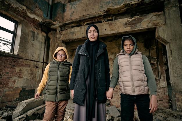 Młoda muzułmanka trzymająca za ręce dwie córki