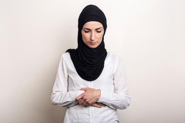 Młoda muzułmanka ubrana w białą koszulę i modląc się hidżab