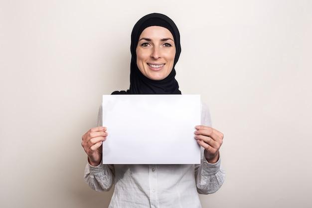 Młoda muzułmanka w białej koszuli i hidżabie trzyma pustą kartkę papieru z uśmiechem