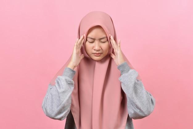 Młoda muzułmanka z bólem głowy trzyma ręce za skronie. koncepcja zdrowia, migreny i bólu głowy, na białym tle na różowym tle