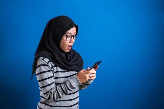 Młoda muzułmanka zszokowana, patrząc na swój telefon na niebieskim tle