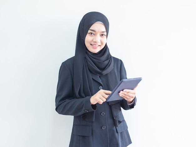 Młoda muzułmańska biznesowej kobiety mienia pastylka