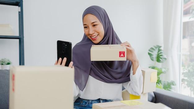 Młoda muzułmańska bizneswoman blogger za pomocą aparatu w telefonie komórkowym do nagrywania vlog wideo na żywo recenzja produktu w domowym biurze.