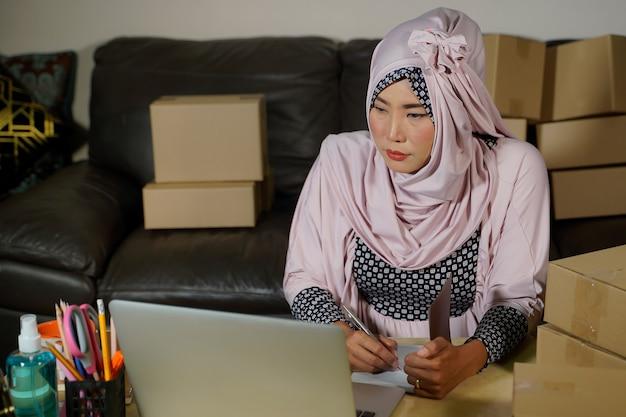 Młoda muzułmańska bizneswoman z azji sprawdza zamówienia na produkty magazynowe i zapisuje je na swoim tablecie w domowym biurze. właściciel małej firmy wysyła rynek internetowy podczas epidemii covid-19 koncepcja