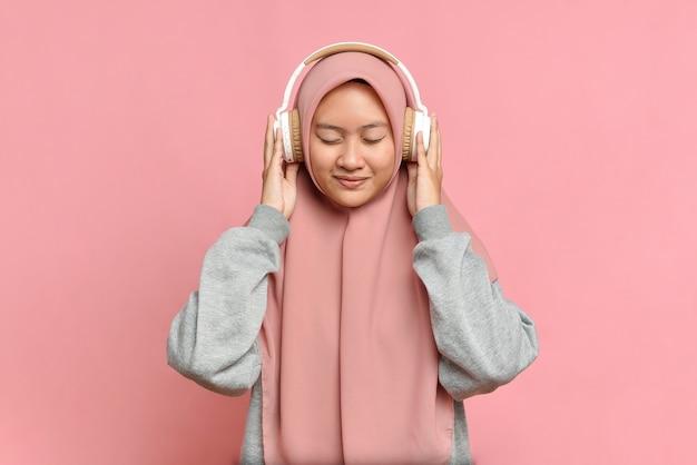 Młoda muzułmańska dziewczyna słucha swojej ulubionej muzyki w białych słuchawkach, zamykając oczy z przyjemności, przyjemności, miłośnika muzyki, na różowym tle