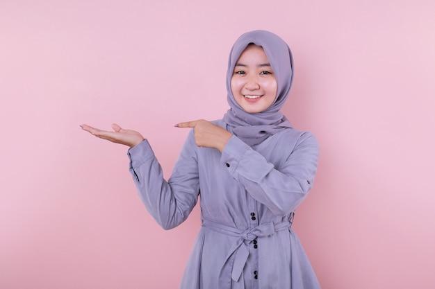 Młoda muzułmańska dziewczyna, wskazując ręką i wesoły uśmiech