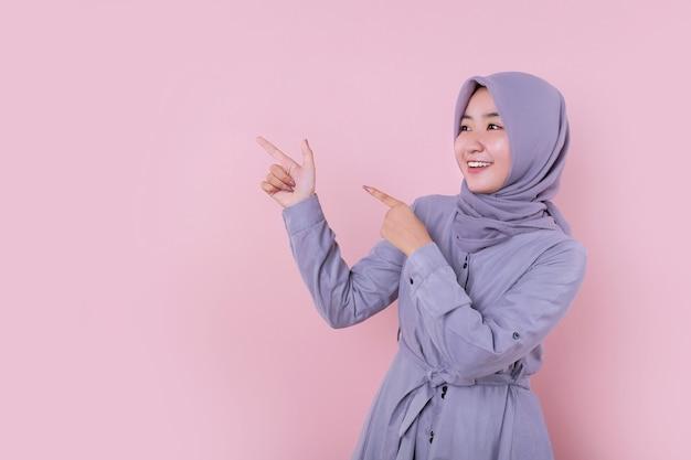 Młoda muzułmańska dziewczyna wskazująca na lewy bok