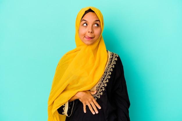 Młoda muzułmańska kobieta na białym tle na niebieskiej ścianie dotyka brzucha, uśmiecha się delikatnie, koncepcja jedzenia i satysfakcji.