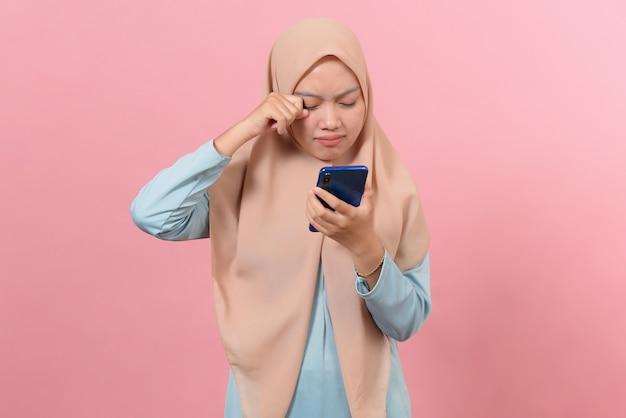Młoda muzułmańska kobieta płacze patrząc na smartfona na białym tle na różowym tle