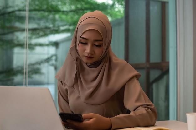 Młoda muzułmańska kobieta robi pracę, poważne uczucie, zajęty czas w biurze