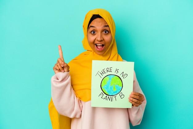 Młoda muzułmańska kobieta trzyma a nie ma afisz planety b na białym tle na niebieskim tle o jakiś świetny pomysł, pojęcie kreatywności.