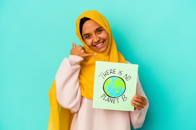 Młoda muzułmańska kobieta trzyma a nie ma planety b afisz na białym tle na niebieskim tle pokazujący gest połączenia z telefonem komórkowym palcami.