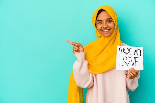 """Młoda muzułmańska kobieta trzyma afisz """"made with love"""" na białym tle na niebieskim tle, uśmiechając się i wskazując na bok, pokazując coś w pustej przestrzeni."""