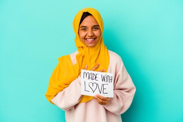 Młoda muzułmańska kobieta trzyma afisz wykonane z miłością na białym tle na niebieskim tle śmiechu i zabawy.
