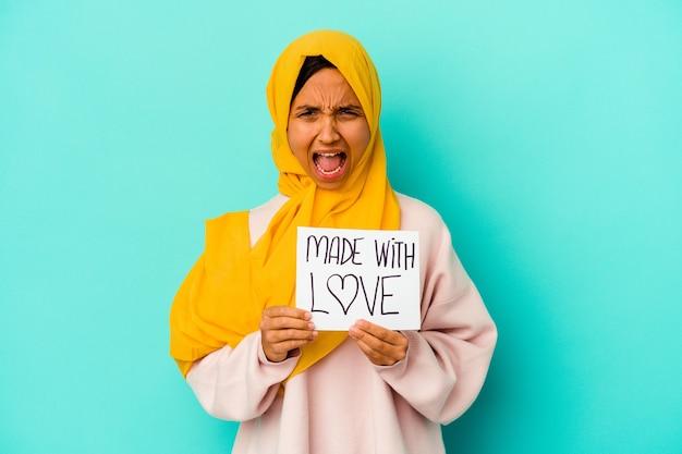 Młoda muzułmańska kobieta trzyma afisz wykonany z miłością na białym tle na niebieskim tle krzyczy bardzo zły i agresywny.