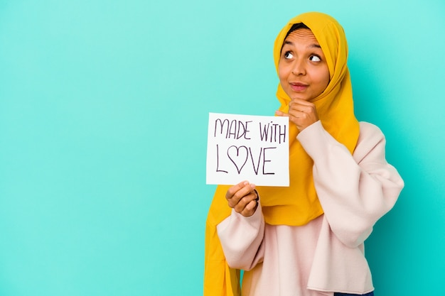 Młoda muzułmańska kobieta trzyma afisz wykonany z miłością na białym tle na niebieskim tle, patrząc w bok z wyrazem wątpliwości i sceptycyzmu.