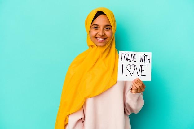 Młoda muzułmańska kobieta trzyma afisz wykonany z miłością na białym tle na niebieskim tle szczęśliwa, uśmiechnięta i wesoła.