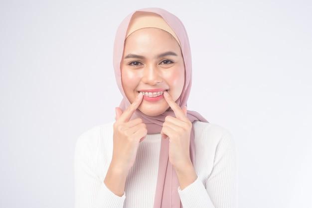 Młoda muzułmańska kobieta trzyma kolorowy uchwyt na zęby na białym tle studio, opieki stomatologicznej i koncepcji ortodontycznej.