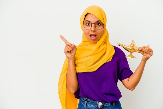 Młoda muzułmańska kobieta trzyma lampę na białym tle na białej ścianie, wskazując w bok