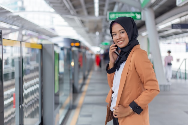 Młoda muzułmańska kobieta używa telefon na skytrain staci.
