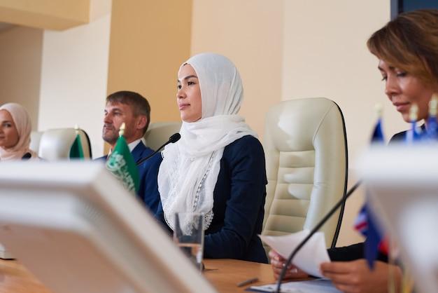 Młoda muzułmańska mówczyni i jej zagraniczni koledzy siedzą przed publicznością i słuchają ich pytań na konferencji