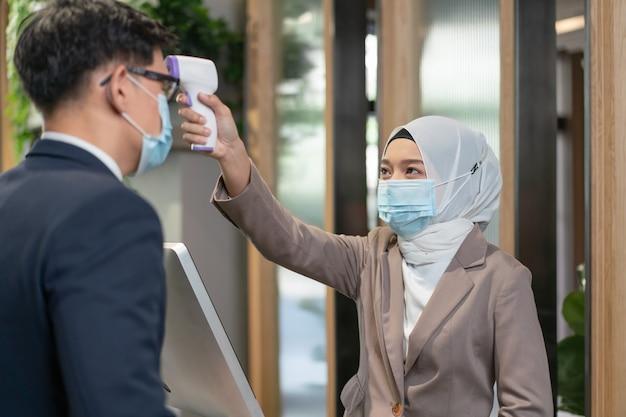 Młoda muzułmańska recepcjonistka za pomocą termometru skanującego w podczerwieni do sprawdzenia temperatury ciała z biznesmenem przed pójściem do biura podczas pandemii koronawirusa