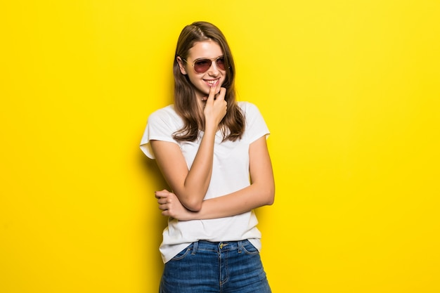 Młoda myśląca dama w białej koszulce i niebieskich dżinsach pozostaje przed żółtym tłem studia