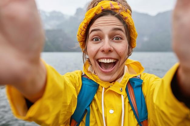 Młoda, nadmiernie wzruszająca kobieta w żółtej kurtce i opasce, rozciąga ręce z nierozpoznawalnym urządzeniem