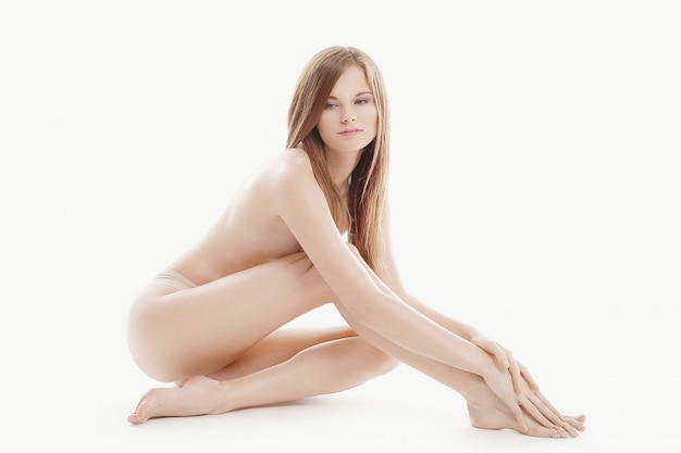 Młoda naga kobieta siedzi na podłodze, koncepcja pielęgnacji ciała i skóry