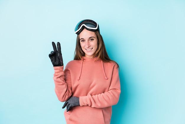 Młoda narciarki kobieta pokazuje numer dwa z palcami