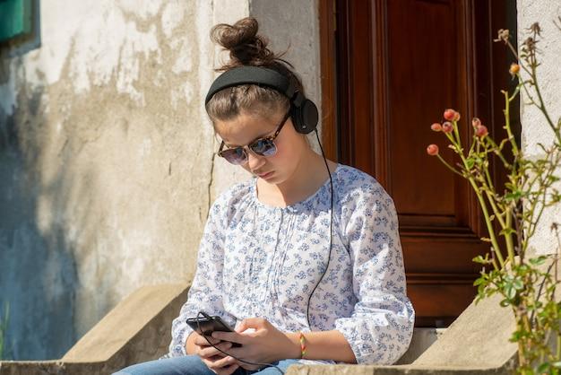 Młoda nastolatek dziewczyna słucha muzyczny plenerowego z okularami przeciwsłonecznymi