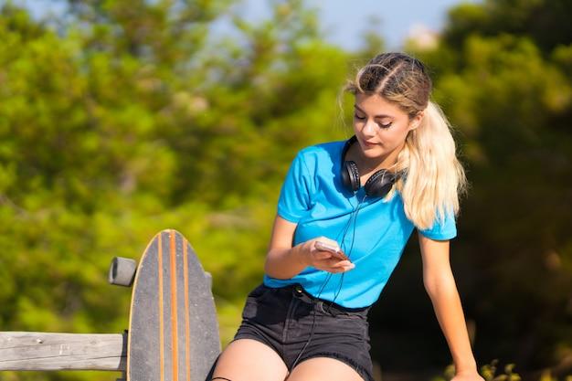 Młoda nastolatek dziewczyna z łyżwą przy outdoors używa telefon komórkowego