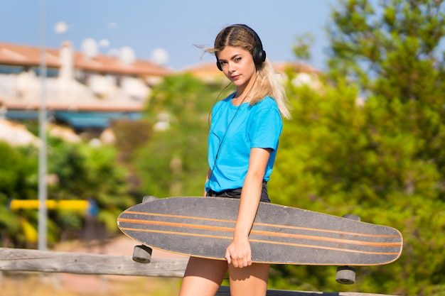 Młoda nastolatek dziewczyna z łyżwowym słuchaniem muzyka z hełmofonami przy outdoors