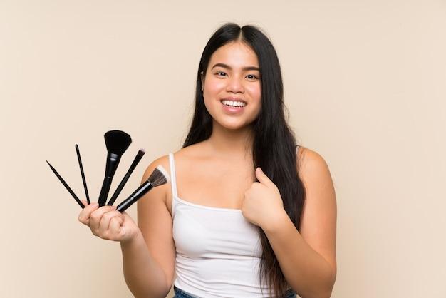 Młoda nastolatka azjatyckich dziewczyna trzyma dużo pędzla do makijażu z niespodzianką wyraz twarzy