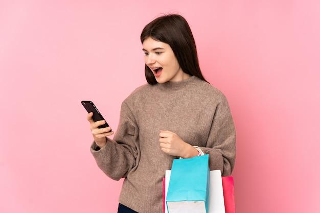 Młoda nastolatka dziewczyny nad różową ścianą trzyma torby na zakupy i pisze wiadomość ze swoim telefonem komórkowym do przyjaciela
