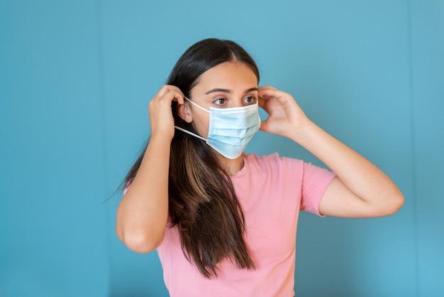 Młoda nastolatka nosząca jednorazową maskę na twarz, zakładając gumkę za uszy podczas pandemii covid-19
