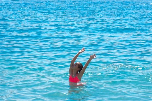 Młoda nastolatka pływa i bawić się w morzu