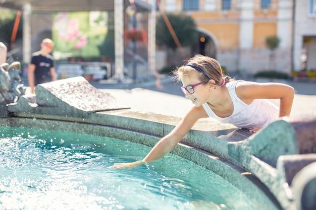 Młoda nastolatka rozpryskuje wodę z fontanny w mieście w upalny letni dzień.