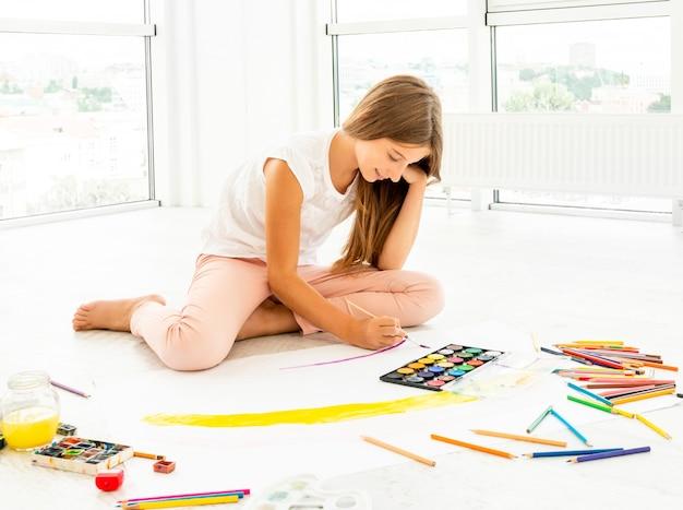 Młoda nastolatka siedzi, malując na papierze