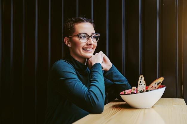 Młoda nastolatka siedzi w restauracji obok okna, opierając się na stole i patrząc przez okno koryta. przed nią miska z pyszną sałatką.