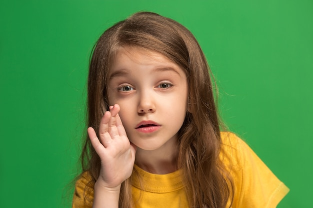 Młoda nastolatka szepcze sekret za jej ręką na zielonym tle