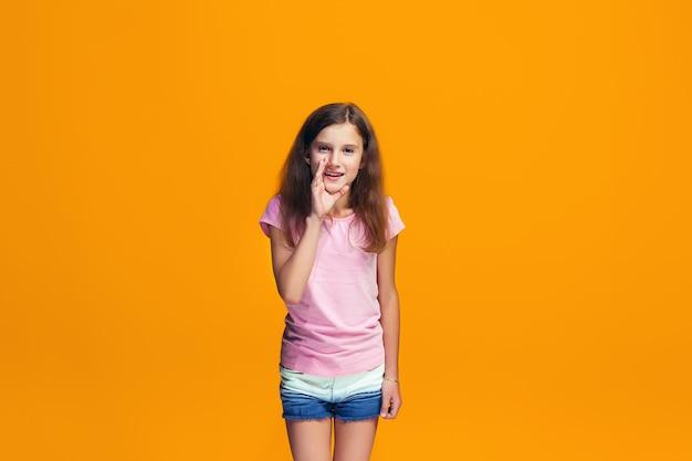 Młoda nastolatka szepcze tajemnicę za ręką nad pomarańczową przestrzenią