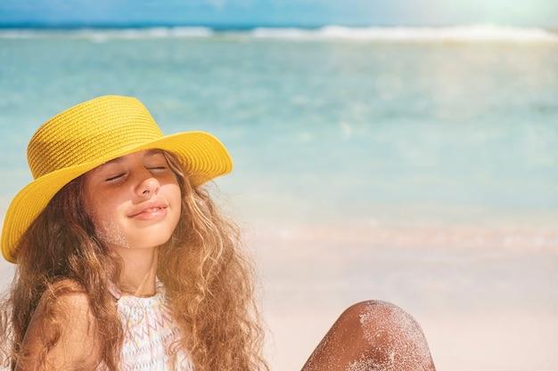 Młoda nastolatka w bikini i żółtym kapeluszu. piękna dziewczyna z długimi włosami w żółtym kapeluszu nad oceanem. letnie wakacje i koncepcja podróży