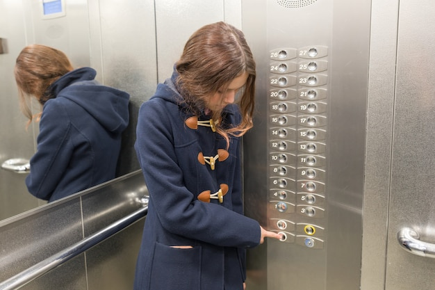 Młoda nastolatka w windzie, naciska przycisk windy