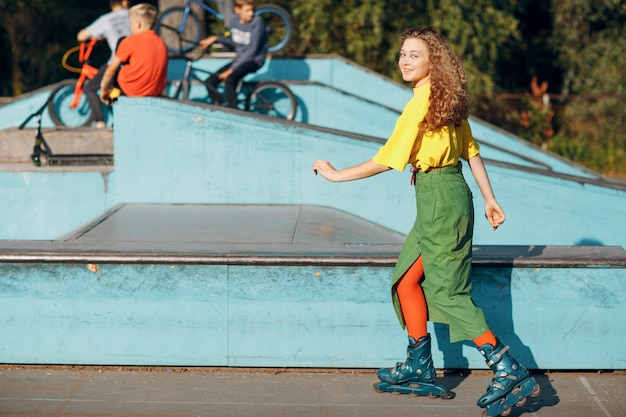 Młoda nastolatka w zielono-żółtych ubraniach i pomarańczowych pończochach z kręconymi fryzurami na rolkach w skate parku