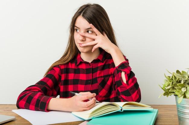 Młoda nastolatka wraca do rutyny, odrabiając zadania domowe, mruga palcami w kamerę