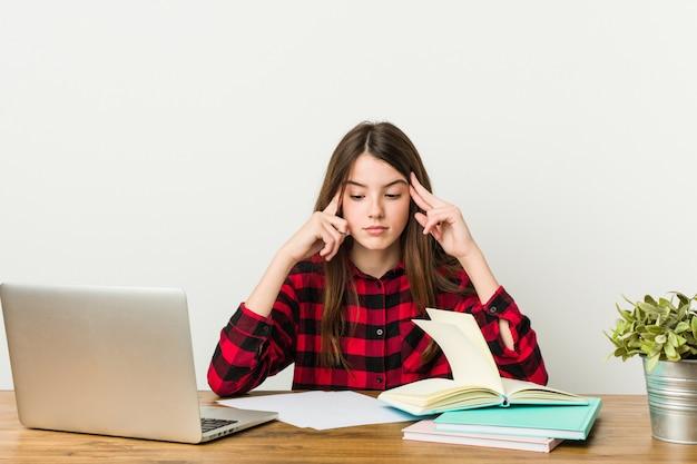 Młoda nastolatka wraca do rutyny, odrabiając zadanie domowe, skupiając się na zadaniu.