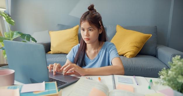 Młoda nastolatka z azji z laptopem do codziennego użytku uczy się online pisać zeszyt wykładowy do testu końcowego w salonie w domu