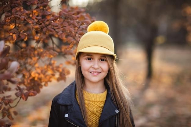 Młoda nastolatka z długimi blond włosami w żółty sweter, kapelusz i skórzaną kurtkę pozowanie w parku jesień. skopiuj miejsce